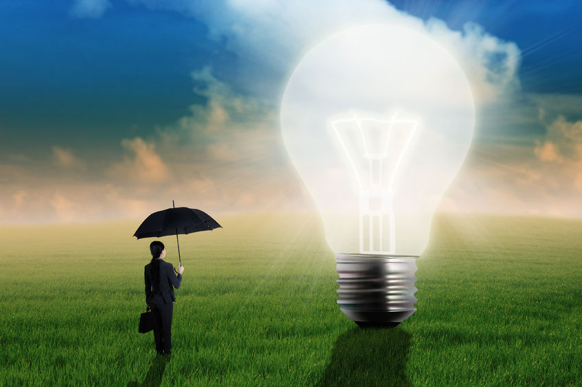 30803923 - young businesswoman standing on the meadow with a bulb as a symbol of creative thinking